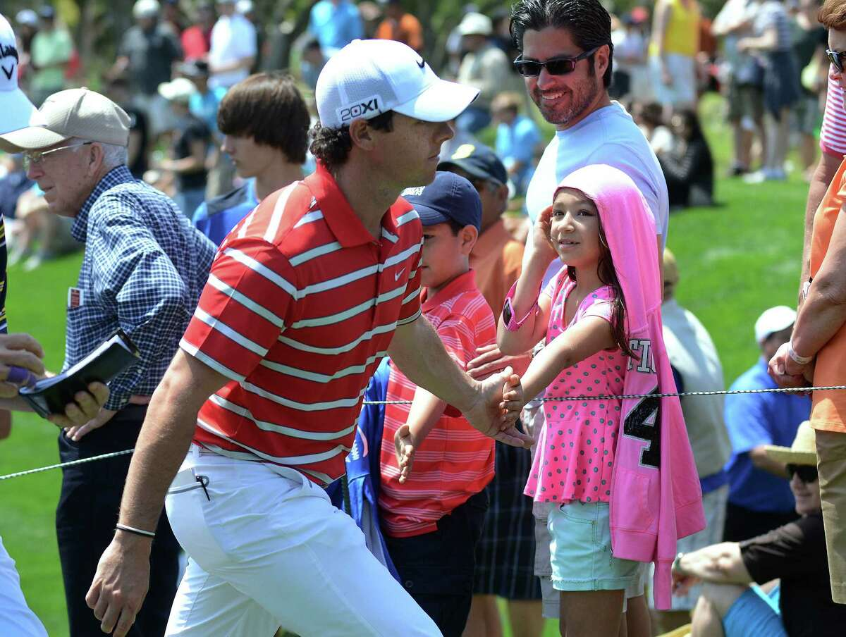 Golfer Rory McIlroy greets a child as he leaves the 8th hole during the third round of the Valero Texas Open at TPC San Antonio's AT&T Oaks Course on Saturday, April 6, 2013.