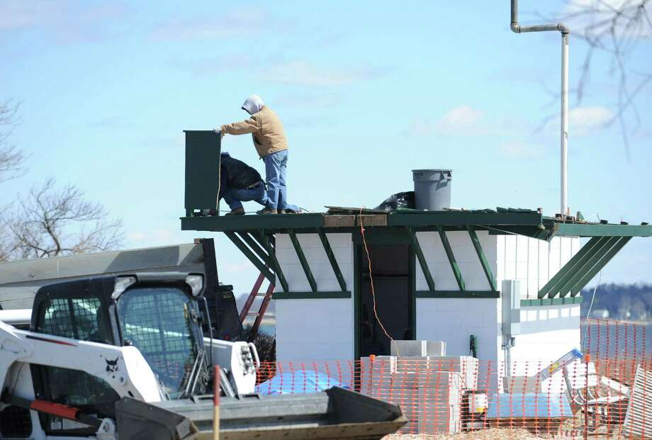 Workers dismantle the top portion of the Greenwich Police sub-station building, also known as the observation tower, near the entrance to Greenwich Point Tuesday, April 2, 2013. The top part, which was damaged and weakened by Hurricane Sandy last fall, is being removed and the building will be topped with a new roof. There has been a structure at the site since the World War II era, when it was a lookout tower manned by volunteers to watch for enemy aircraft. ItâÄôs also been used by lifeguards. Most recently, police refurbished the building to house a small contingent of officers to provide a greater police presence at the Point. Photo: Bob Luckey / Greenwich Time