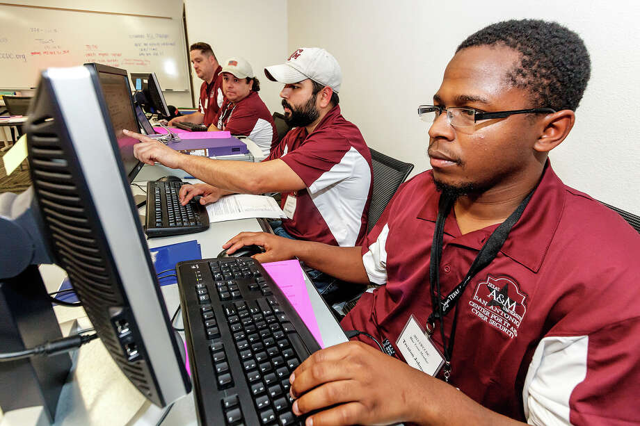 Texas A&M University-San Antonio students Trenton Johnson (from right), Tony Salazar, Eric Martinez and Eric Breedlove work to defend their computer network from attack. Photo: Marvin Pfeiffer, San Antonio Express-News / Express-News 2013