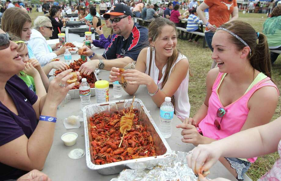 Mar Carmona smiles as she tries to eat crawfish for the first time with McKenzee Lilly during the Pearland Crawfish Festival on Saturday, April 6, 2013, in Pearland. The Pearland Crawfish Festival served up spicy crawfish, live Zydeco music, and a variety of vendors. The festival opens Sunday, March 7th, from 11 a.m.- 6 p.m. off south 288 between FM 2234 and FM 518. Photo: Mayra Beltran, Houston Chronicle / © 2013 Houston Chronicle