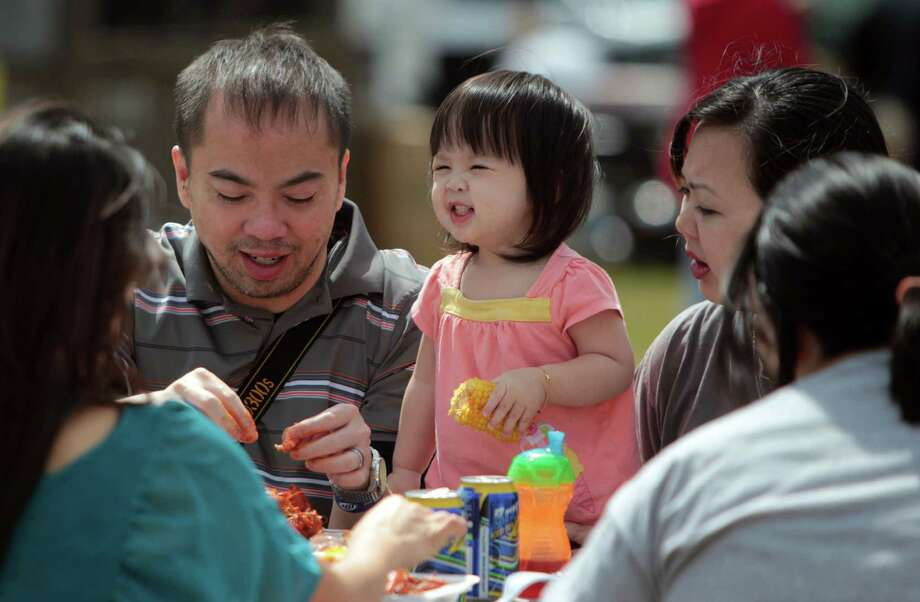 Tom Nguyen, and Tina Nguyen feed their daughter Sophia Nguen, 1, corn on the cob and crawfish meat during the Pearland Crawfish Festival on Saturday, April 6, 2013, in Pearland. Photo: Mayra Beltran, Houston Chronicle / © 2013 Houston Chronicle