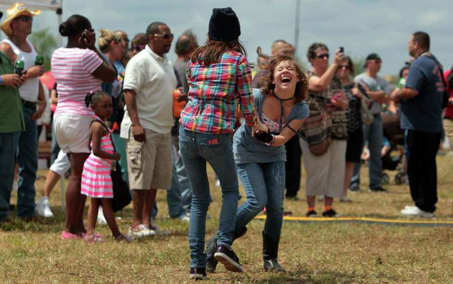 Alexus Gutierrez, 12, dances with her sister Chelby Castillo, 14, of Alvin, to Zydeco music from the Bon Ton Mickey band during the Pearland Crawfish Festival on Saturday, April 6, 2013, in Pearland. Photo: Mayra Beltran, Houston Chronicle / © 2013 Houston Chronicle