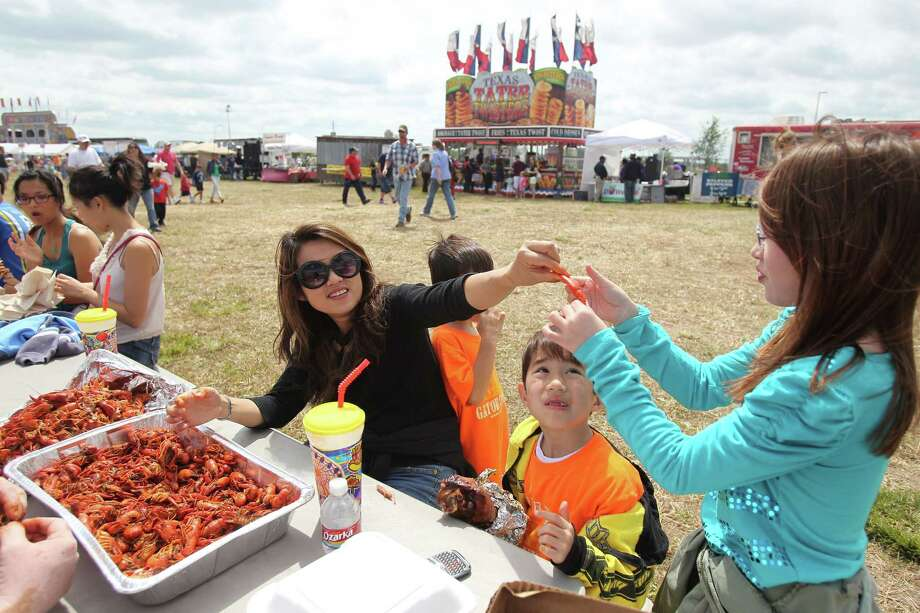 Ntanhthy Tran hands over crawfish claw to daughter Christina Lewellyn as son Joshua Lewellyn looks on during the Pearland Crawfish Festival on Saturday, April 6, 2013, in Pearland. Photo: Mayra Beltran, Houston Chronicle / © 2013 Houston Chronicle