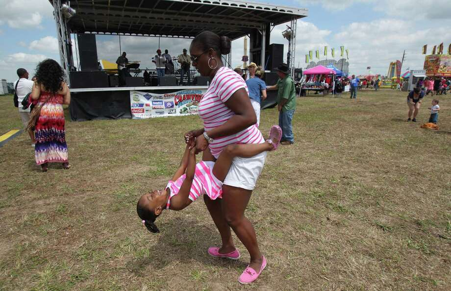 Autumn Yancy, 5, smiles while dancing with her mother Tasha Cross during the Pearland Crawfish Festival on Saturday, April 6, 2013, in Pearland. Photo: Mayra Beltran, Houston Chronicle / © 2013 Houston Chronicle