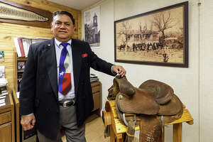 "Rudi R. Rodriguez, avid Tejano historian and the founder and president of TexasTejano.com, stands with a photo in his office taken in 1914 of one of his ancestors, Jose Policarpio ""Polly"" Rodriguez with family and friends at a home Polly constructed near Bandera in 1858 and a saddle from Atascosa County once owned by Polly's oldest brother, Jose Justo Rodriguez, in the 1880's to 1890's.  Photo taken Wednesday, April 3, 2013.  MARVIN PFEIFFER/ mpfeiffer@express-news.net"