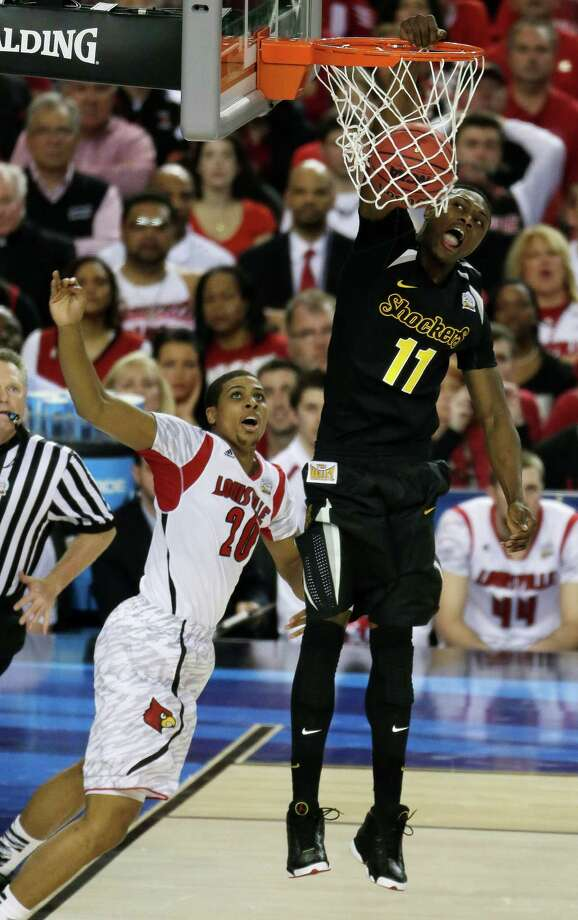 Louisville's Luke Hancock (11) dunks the ball against Louisville's Wayne Blackshear (20) during the first half of the NCAA Final Four tournament college basketball semifinal game Saturday, April 6, 2013, in Atlanta. (AP Photo/Chris O'Meara) Photo: Chris O'Meara, Associated Press / AP