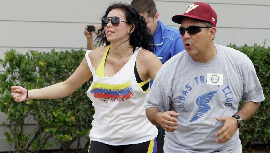 Zumba (R) instructor Tatiana Torrente, left, leads a dance as Jose Beltran, right, follows along during the Zumba (R) Fitness Class for Venezuela fundraising event at Ray Miller Park Saturday, April 6, 2013, in Hockley . Photo: James Nielsen, Houston Chronicle / © 2013 Houston Chronicle