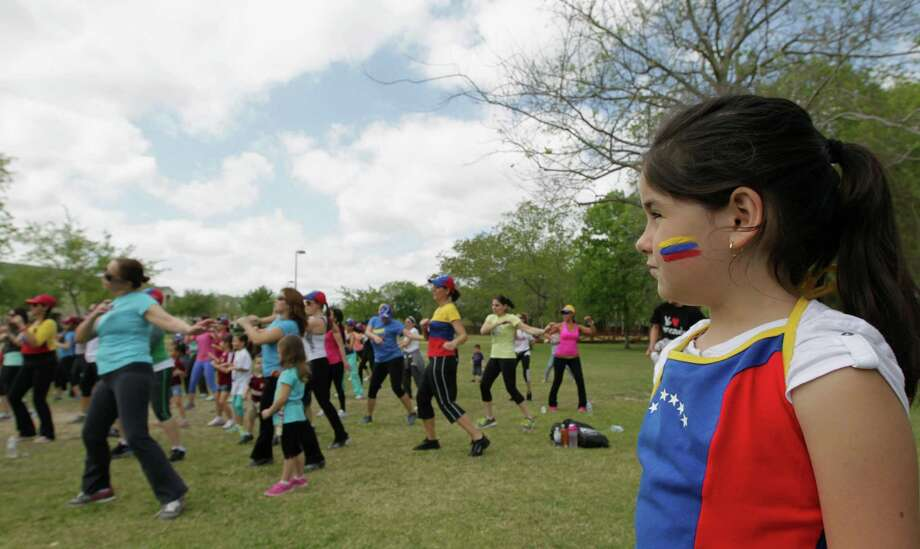 Six-year-old Michelle Demari, right, looks on as people dance during the Zumba (R) Fitness Class for Venezuela fundraising event at Ray Miller Park Saturday, April 6, 2013, in Houston. Photo: James Nielsen, Houston Chronicle / © 2013 Houston Chronicle