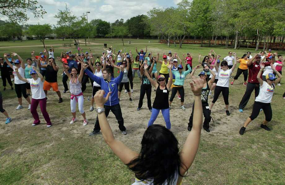 Zumba (R) instructor Tatiana Torrenta center, leads a dance during the Zumba (R) Fitness Class for Venezuela fundraising event at Ray Miller Park Saturday, April 6, 2013, in Houston. Photo: James Nielsen, Houston Chronicle / © 2013 Houston Chronicle