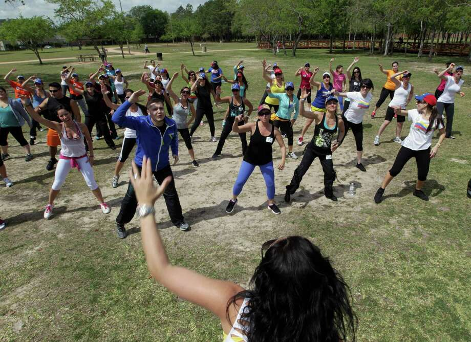 Zumba (R) instructor Tatiana Torrenta, center, leads a dance during the Zumba (R) Fitness Class for Venezuela fundraising event at Ray Miller Park Saturday, April 6, 2013, in Houston. Photo: James Nielsen, Houston Chronicle / © 2013 Houston Chronicle