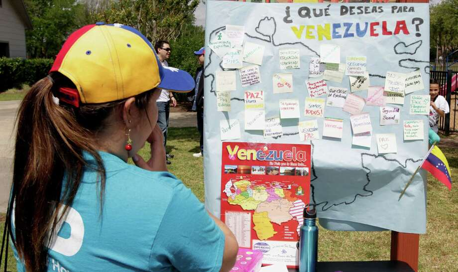 A woman looks over a sign with a map of Venezuela with personalized post it notes during the Zumba (R) Fitness Class for Venezuela fundraising event at Ray Miller Park Saturday, April 6, 2013, in Houston. Photo: James Nielsen, Houston Chronicle / © 2013 Houston Chronicle