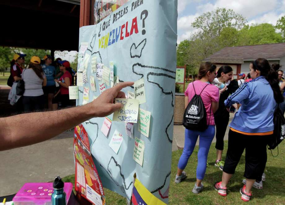 A man posts a note to a sign with a map of Venezuela during the Zumba (R) Fitness Class for Venezuela fundraising event at Ray Miller Park Saturday, April 6, 2013, in Houston. Photo: James Nielsen, Houston Chronicle / © 2013 Houston Chronicle