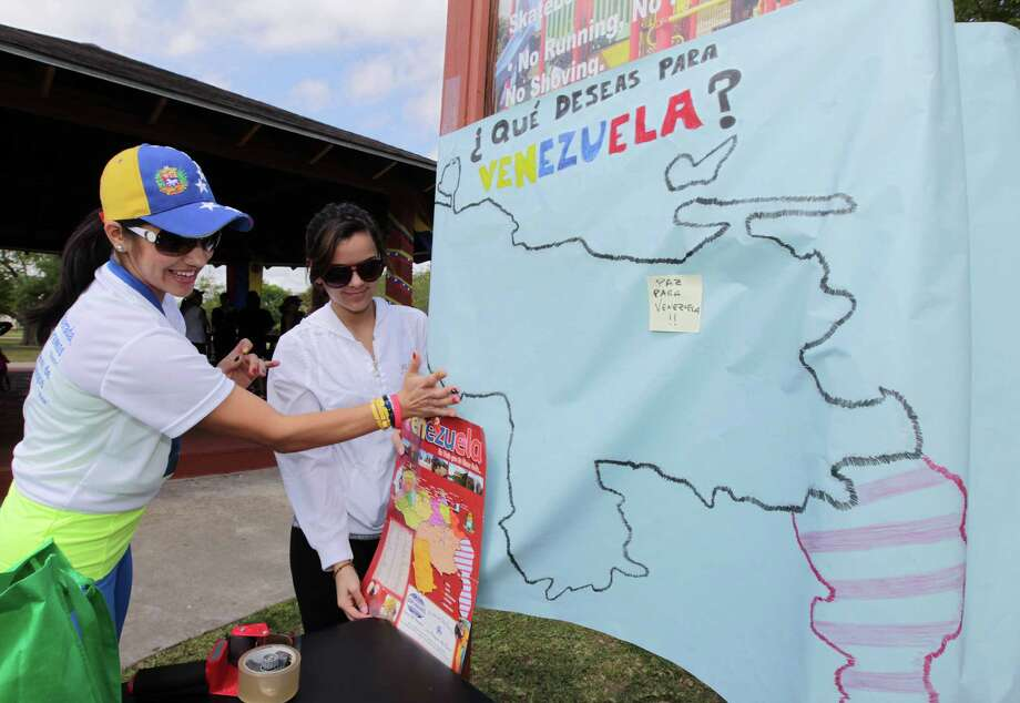 Janette Quintero, left, and Rebecca Ramirez right, post a sign with a map of Venezuela during the Zumba (R) Fitness Class for Venezuela fundraising event at Ray Miller Park Saturday, April 6, 2013, in Houston. Photo: James Nielsen, Houston Chronicle / © 2013 Houston Chronicle