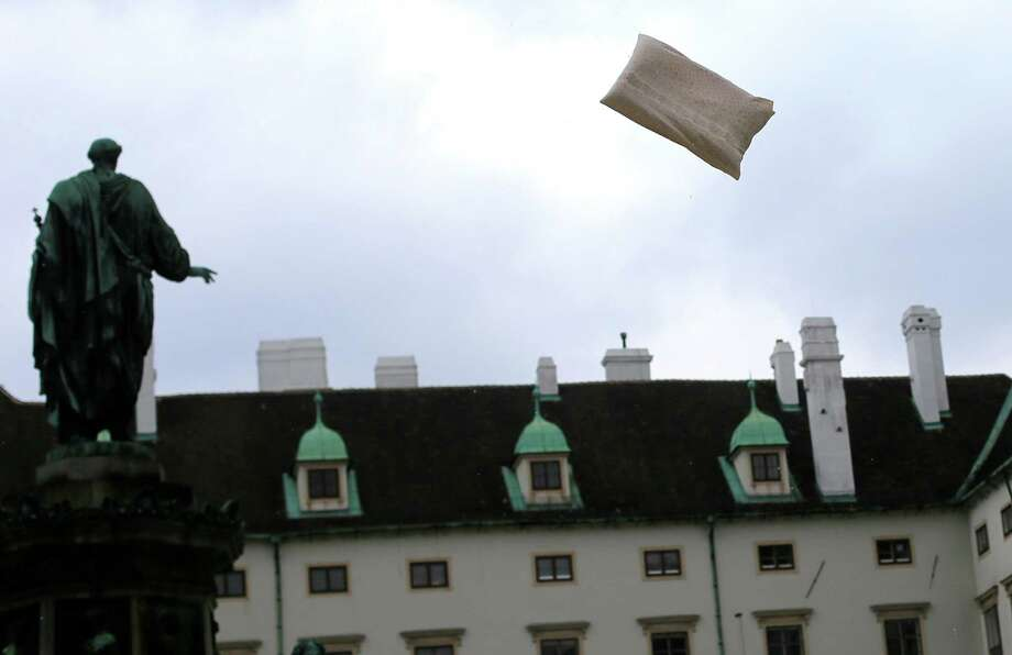 A pillow flies over Vienna's Maria-Theresien-Square during the mass pillow fight event in Vienna, Austria on April 6, 2013, the International Pillow Fight Day. Photo: ALEXANDER KLEIN, AFP/Getty Images / ALEXANDER KLEIN