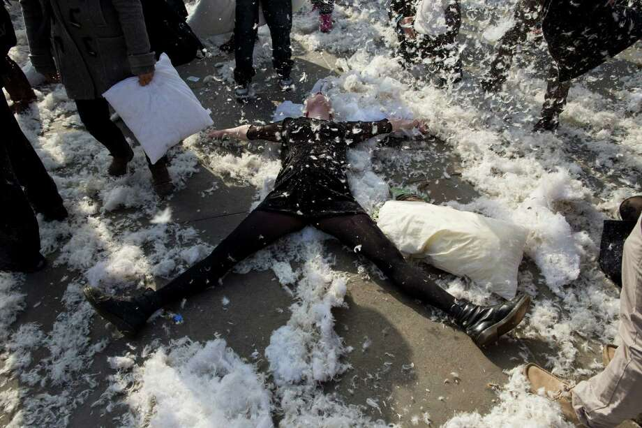 "A woman makes a ""feather angel"" as she takes part in a pillow fight in Trafalgar Square in London, Saturday, April 6, 2013. Photo: Matt Dunham, Associated Press / AP"