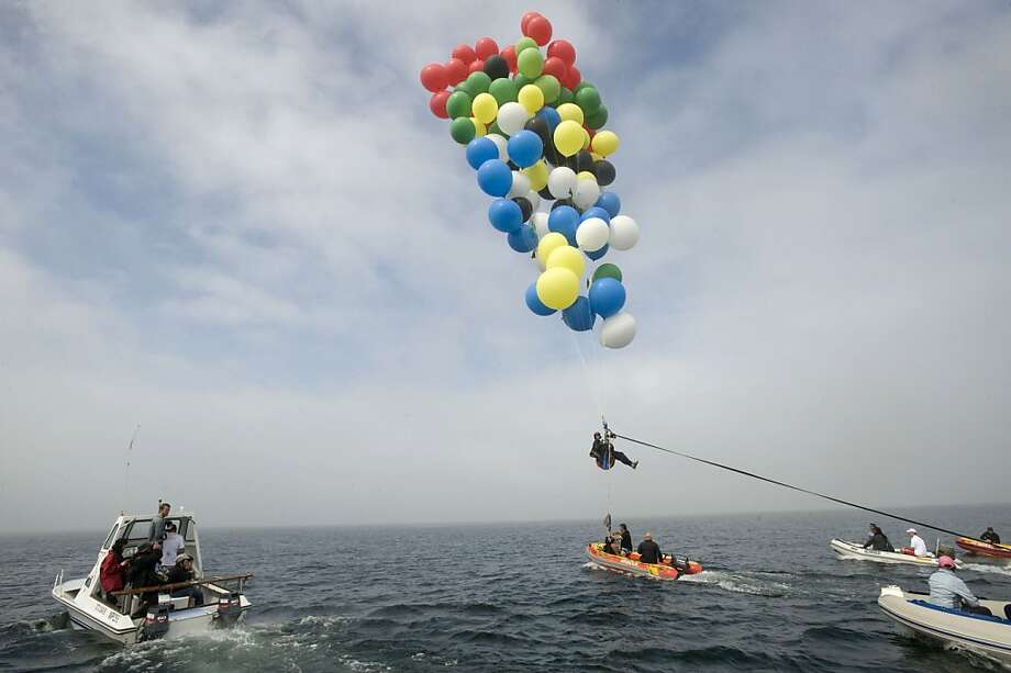 Suspended by helium party balloonstethered to a support boat, Matt Silver-Vallance sails from Nelson Mandela's apartheid island prison across Table Bay to Cape Town, South Africa. The 3.7-mile flight raised funds for a children's hospital named after the former president. Photo: Rodger Bosch, AFP/Getty Images