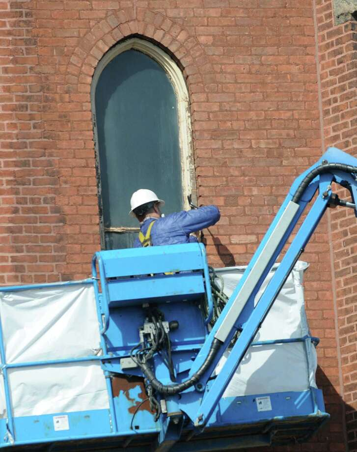 A construction worker hammers at a window frame on St. Patrick's church on Friday, April 5, 2013 in Watervliet, N.Y. (Lori Van Buren / Times Union) Photo: Lori Van Buren