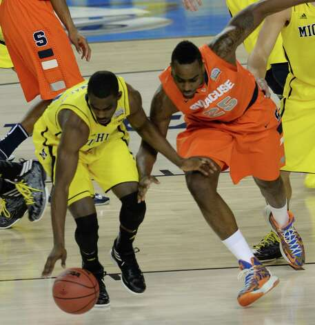 Tim Hardaway Jr. (10) of Michigan and Rakeem Christmas (25) of Syracuse battle for a loose ball in the first half in an NCAA Final Four semifinal at the Georgia Dome in Atlanta, Georgia, Saturday