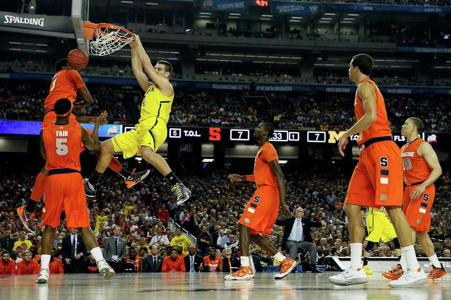 ATLANTA, GA - APRIL 06:  Mitch McGary #4 of the Michigan Wolverines dunks in the first half against Jerami Grant #3 of the Syracuse Orange during the 2013 NCAA Men's Final Four Semifinal at the Georgia Dome on April 6, 2013 in Atlanta, Georgia. Photo: Streeter Lecka, Getty Images / 2013 Getty Images