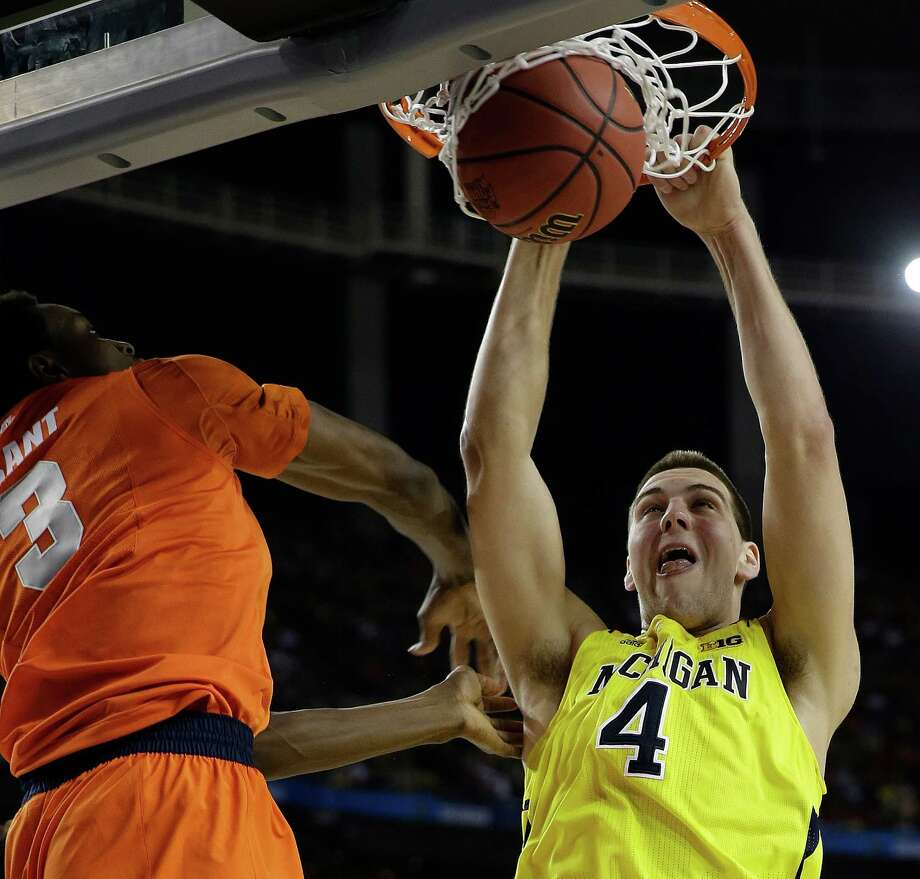 Michigan's Mitch McGary (4) dunks the ball against Syracuse's Jerami Grant (3) during the first half of the NCAA Final Four tournament college basketball semifinal game Saturday, April 6, 2013, in Atlanta. (AP Photo/David J. Phillip) Photo: David J. Phillip, Associated Press / AP