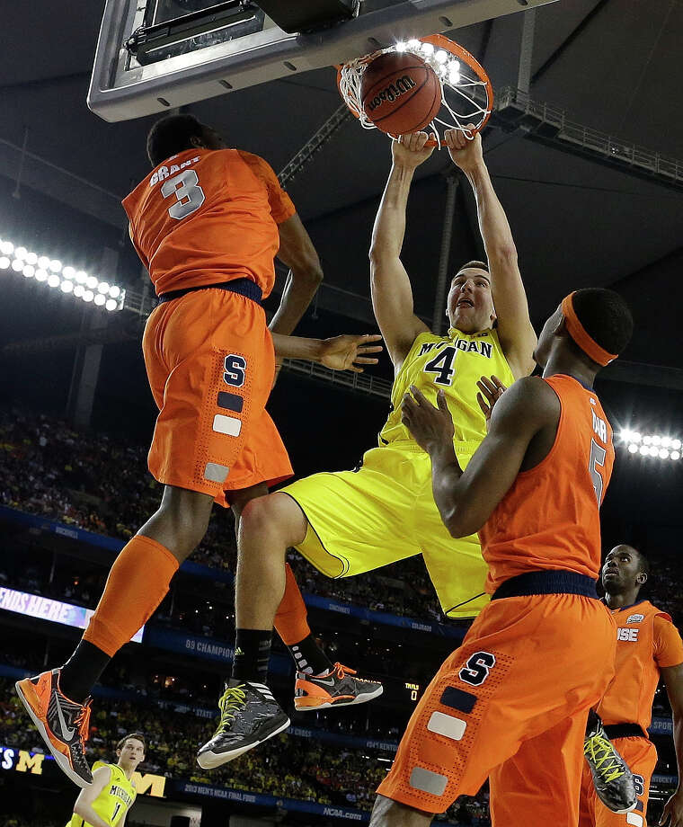 Michigan's Mitch McGary (4) dunks the ball against Syracuse's Jerami Grant (3) and Syracuse's C.J. Fair (5) during the first half of the NCAA Final Four tournament college basketball semifinal game Saturday, April 6, 2013, in Atlanta.  (AP Photo/David J. Phillip) Photo: David J. Phillip, Associated Press / AP
