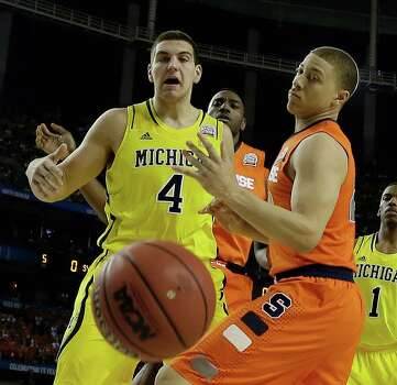 Michigan's Mitch McGary (4) and Syracuse's Brandon Triche (20)vie for a loose ball during the first half of the NCAA Final Four tournament college basketball semifinal game, Saturday, April 6, 2013, in Atlanta. (AP Photo/Charlie Neibergall) Photo: Charlie Neibergall, Associated Press / AP