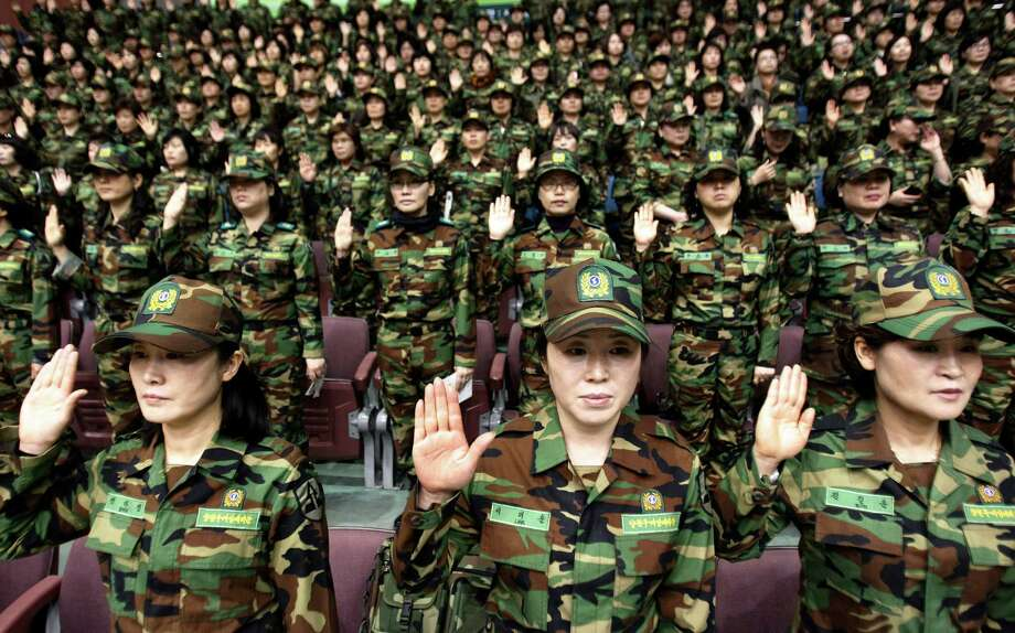South Korean army reservists raise their hands to adopt a resolution against North Korea during a rehearsal for their Foundation Day ceremony at a gymnasium in Seoul, South Korea, Friday, April 5, 2013. About 1,000 reservists denounce North Korean for their escalating threat for war. North Korea has been railing against U.S.-South Korean military exercises that began in March and are to continue until the end of this month. The allies insist the exercises in South Korea are routine, but the North calls them rehearsals for an invasion and says it needs nuclear weapons to defend itself. (AP Photo/Ahn Young-joon) Photo: Ahn Young-joon
