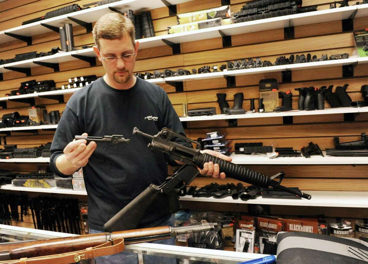 KevinZacharewicz, owner of Zack's Sports, shows how to clean a recently banned AR-15 semi-automatic rifle on Tuesday, April 2, 2013 in Round Lake, N.Y. (Lori Van Buren / Times Union)