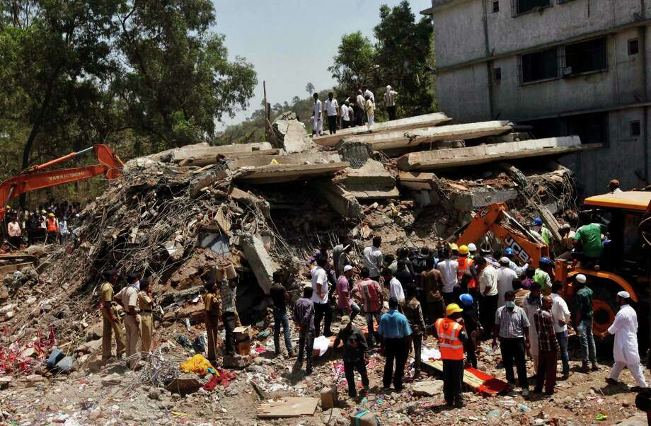 People gather around a heap of debris at the site of a building collapsed as a rescue operation continues on the outskirts of Mumbai, India, Friday, April 5, 2013. A half-finished building that was being constructed illegally in a suburb of India's financial capital collapsed, killing 35 people and injuring more than 50 others, police said Friday. (AP Photo/Rajanish Kakade) Photo: Rajanish Kakade