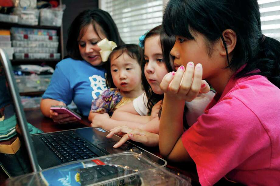 "In this April 4, 2013 photograph, the Smith women, from left, mother Niki Smith, GiGi, 3, Macy Jade, 7 and Guan Ya, 14, use Google Translate on the family laptop to ""speak"" with their new daughter, Guan Ya, in their Rienzi, Miss., home. The Smiths and their children are using the Google Translate program to communicate almost exclusively with Guan Ya, who is deaf. The family uses iPhones, iPods and a laptop, all loaded with the program to write in either English that translates to Chinese or vice-a-versa. (AP Photo/Rogelio V. Solis) Photo: Rogelio V. Solis"