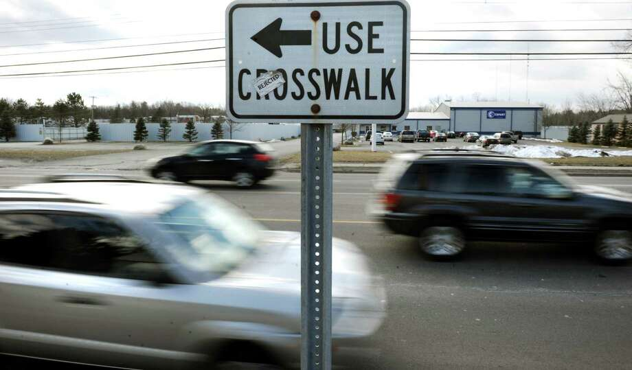 A sign directs pedestrians to the crosswalk near the Blu-Bell Motel on Central Avenue on Tuesday, March 26, 2013, in Colonie, N.Y. (Cindy Schultz / Times Union) Photo: Cindy Schultz / 00021725A
