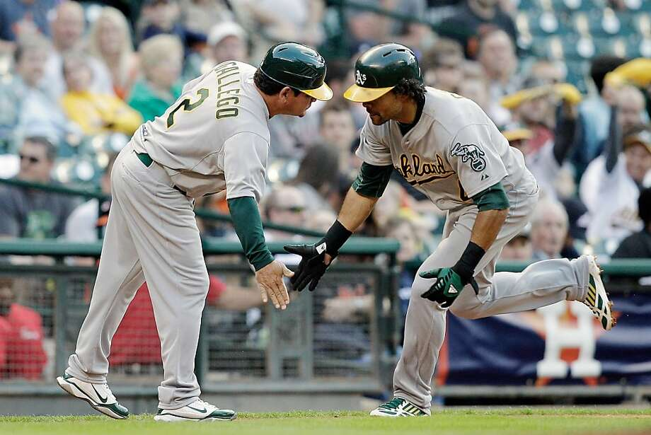 Coach Mike Gallego congratulates Coco Crisp as he rounds third after hitting a solo home run off Houston's Bud Norris in the fourth. Photo: Bob Levey, Getty Images
