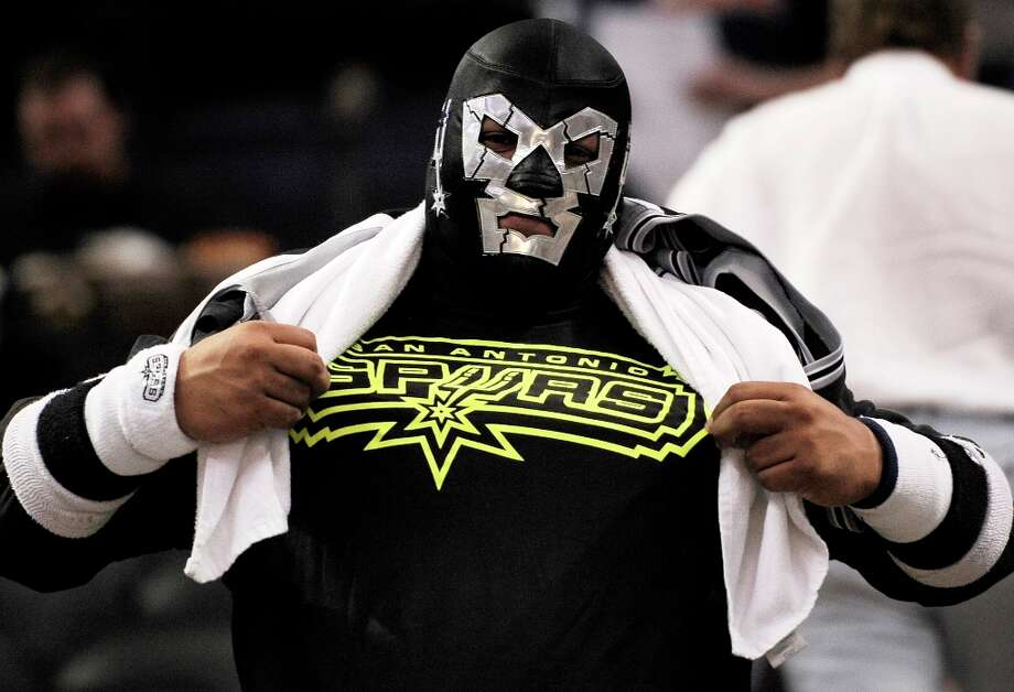 A Spurs fan wearing a luchador mask shows his team spirit before the game against the Atlanta Hawks, Saturday, April 6, 2013, at the AT&T Center. Photo: Darren Abate, Associated Press / FR115 AP
