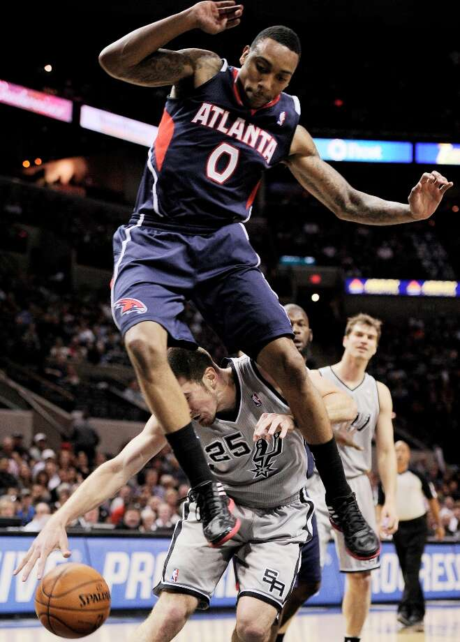 Atlanta Hawks\' Jeff Teague (0) leaps over the Spurs\' Nando De Colo during the first half Saturday, April 6, 2013, at the AT&T Center. Photo: Darren Abate, Associated Press / FR115 AP