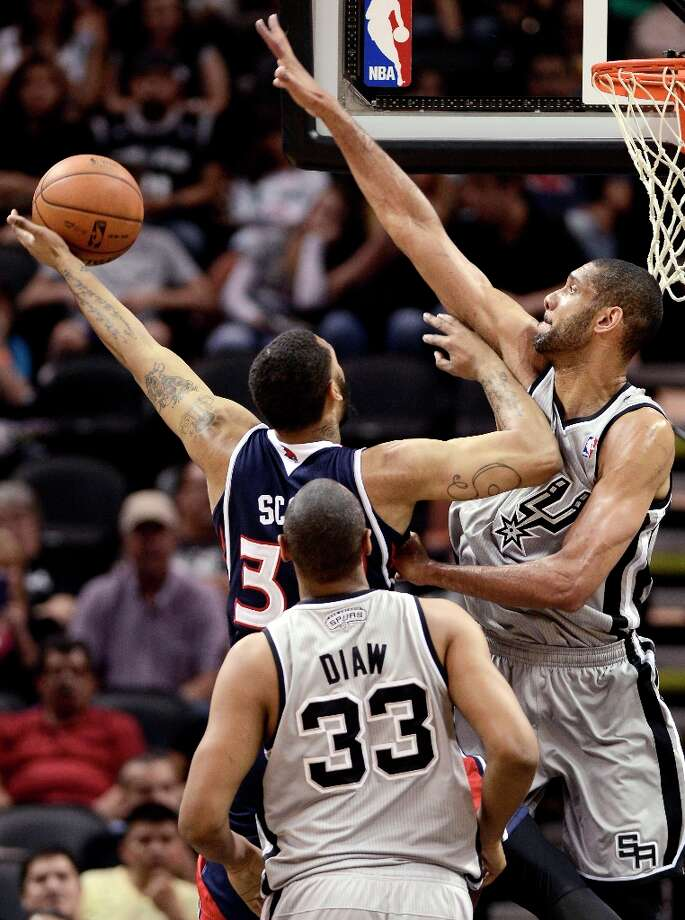 Atlanta Hawks\' Mike Scott (center) tries to shoot between the Spurs\' Tim Duncan (right) and Boris Diaw during the first half Saturday, April 6, 2013, at the AT&T Center. Photo: Darren Abate, Associated Press / FR115 AP
