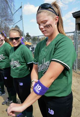 Courtney Hilligas puts on a Dianna Rivers' number 19 wrist band as the Shen softball team at the starts their game with Saratoga High at Geyser Road Field in Saratoga Springs Friday April 5, 2013. This was their first game without Dianna Rivers, who was killed in December car crash.  (John Carl D'Annibale / Times Union) Photo: John Carl D'Annibale / 10021862A