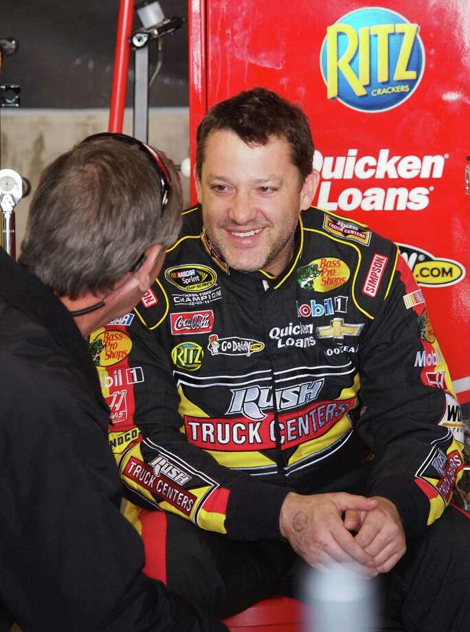 Driver Tony Stewart talks with a crew member in the garage after practice for Sunday's NASCAR Sprint Cup series auto race at Martinsville Speedway in Martinsville, Va., Saturday, April 6, 2013. (AP Photo/Steve Sheppard) Photo: Steve Sheppard