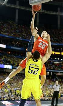 Brandon Triche (20) of the Syracuse Orange is called for charging after running into Jordan Morgan (52) of the Michigan Wolverines late in the game in an NCAA Final Four semifinal at the Georgia Dome in Atlanta, Georgia, Saturday, April 6, 2013. Michigan advanced to the finals, 61-56. (Mark Cornelison/Lexington Herald-Leader/MCT) Photo: Mark Cornelison, McClatchy-Tribune News Service / Lexington Herald-Leader