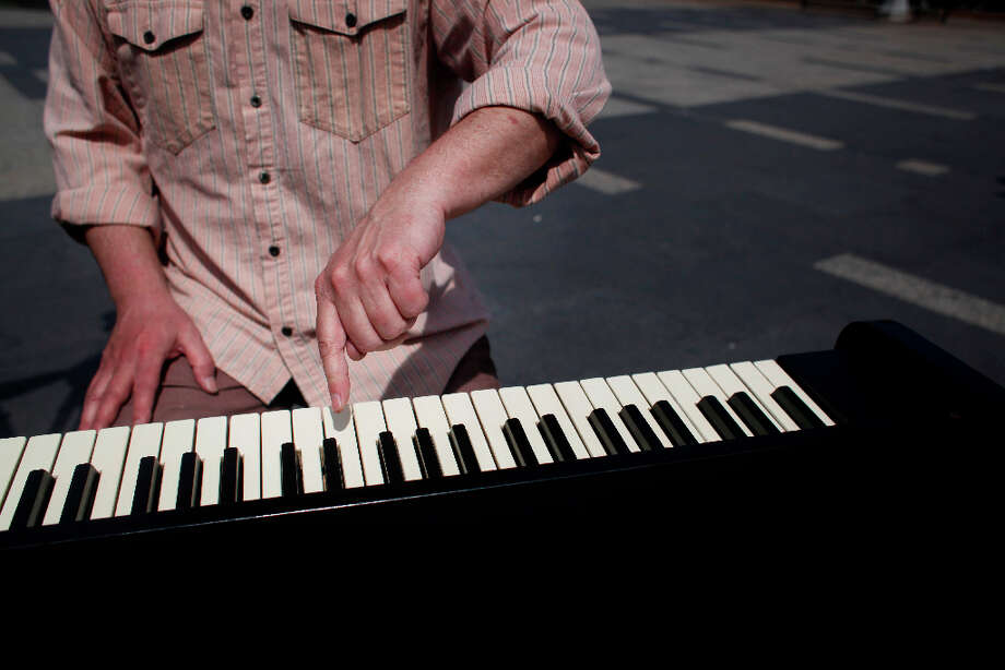 Gary Skaggs tests the keys on his piano bike while riding in San Francisco. Photo: Mike Kepka, The Chronicle / ONLINE_YES