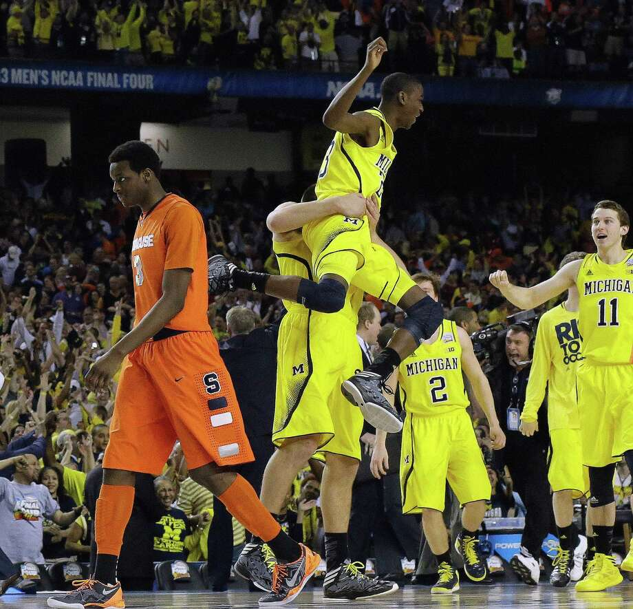Michigan's Caris LeVert (23) celebrates with team mates as Syracuse's Jerami Grant (3) walks off the court during the second half of the NCAA Final Four tournament college basketball semifinal game Saturday, April 6, 2013, in Atlanta. Michigan won 61-56. (AP Photo/David J. Phillip) Photo: David J. Phillip