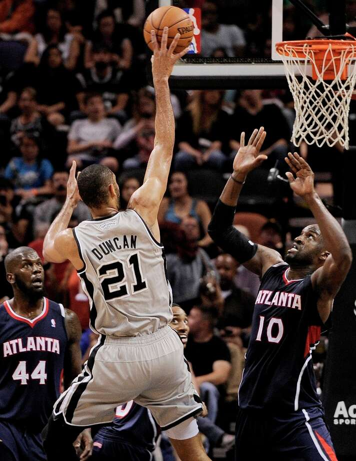 The Spurs\' Tim Duncan (center) shoots against Atlanta Hawks\' Johan Petro (right) and Ivan Johnson during the second half Saturday, April 6, 2013, at the AT&T Center. Spurs won 99-97. Photo: Darren Abate, Associated Press / FR115 AP