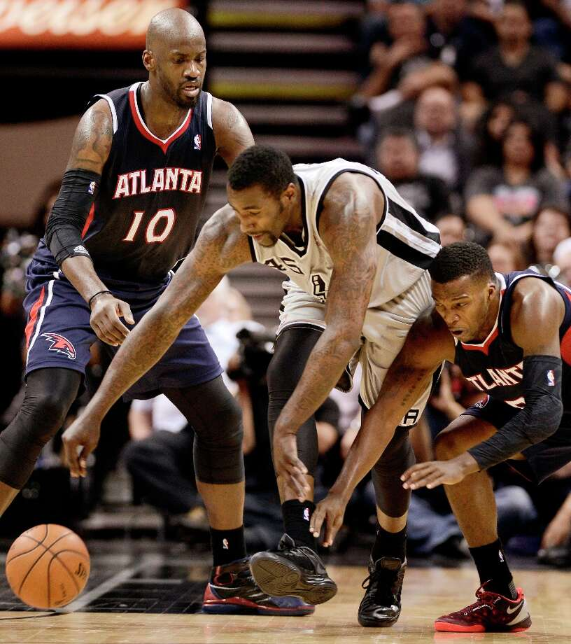 The Spurs\' DeJuan Blair (center) chases the loose ball against Atlanta Hawks\' Johan Petro (left) and Shelvin Mack during the second half Saturday, April 6, 2013, at the AT&T Center. San Antonio won 99-97. Photo: Darren Abate, Associated Press / FR115 AP