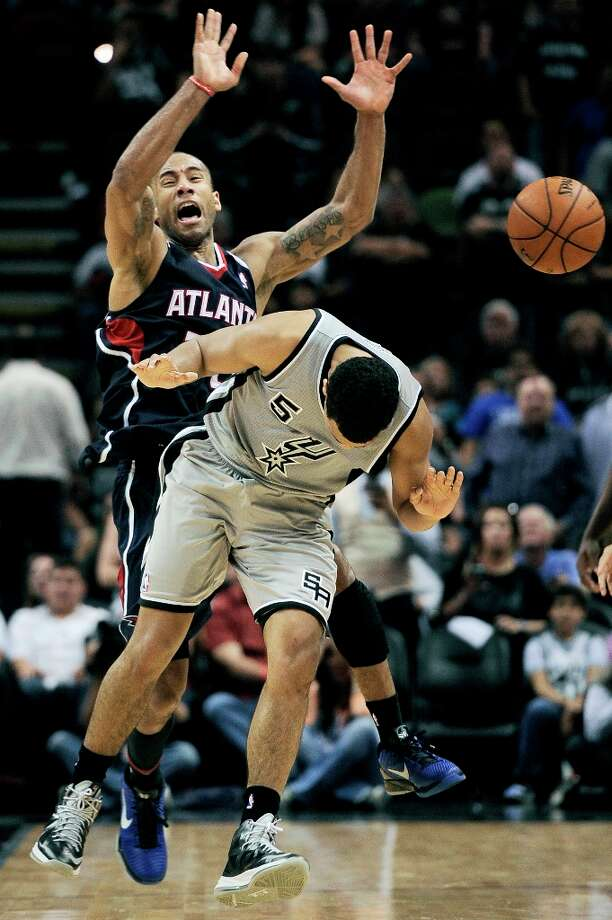 Atlanta Hawks\' Dahntay Jones (rear) is fouled by the Spurs\' Cory Joseph in the closing seconds Saturday, April 6, 2013, at the AT&T Center. The Spurs won 99-97. Photo: Darren Abate, Associated Press / FR115 AP