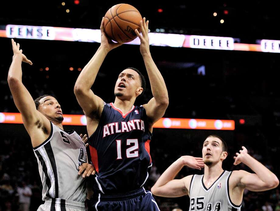 Atlanta Hawks\' John Jenkins (12) shoots against the Spurs\' Cory Joseph (left) and Nando De Colo during the second half Saturday, April 6, 2013, at the AT&T Center. San Antonio won 99-97. Photo: Darren Abate, Associated Press / FR115 AP