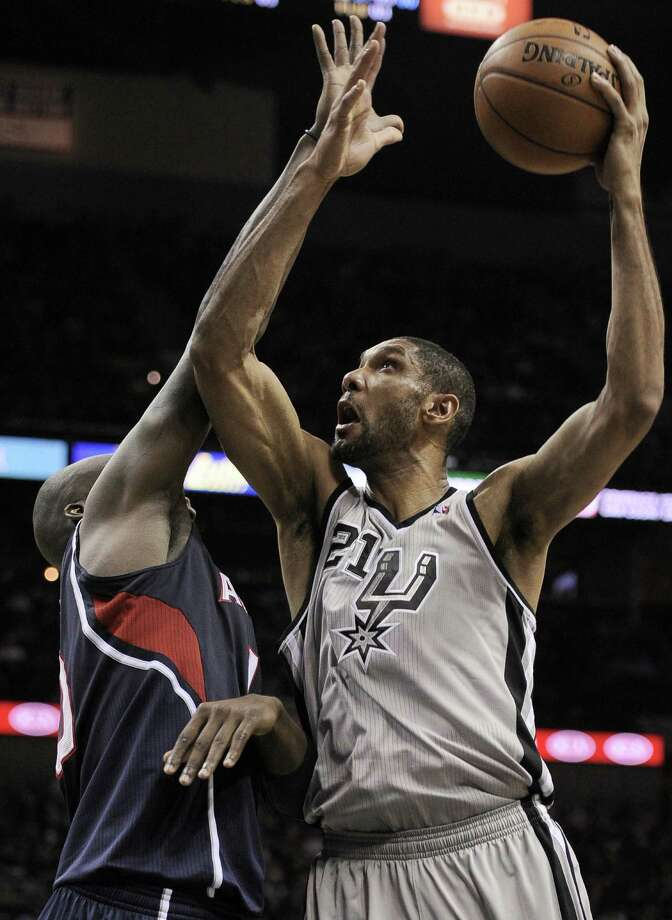 Tim Duncan looks for a shot with his left hand over Atlanta's Johan Petro during the Spurs' victory that clinched the Southwest Division. Photo: Darren Abate / Associated Press