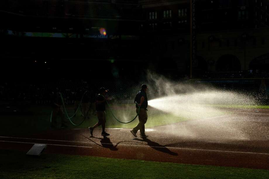 Groundskeepers spay water on the infield before the Astros game against the Oakland Athletics. Photo: Smiley N. Pool, Houston Chronicle / © 2013  Smiley N. Pool