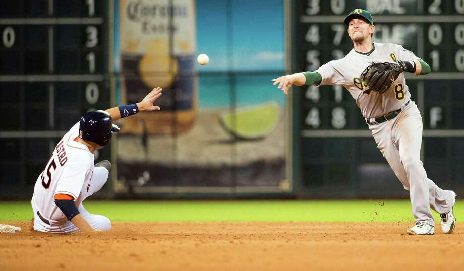 Athletics shortstop Jed Lowrie makes a relay over Astros catcher Jason Castro to complete a double play during the sixth inning. Photo: Smiley N. Pool, Houston Chronicle / © 2013  Smiley N. Pool