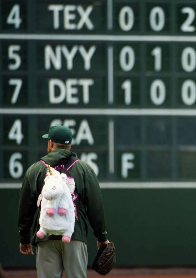 Oakland relief pitcher Sean Doolittle wears a unicorn backpack as he heads out to the bullpen before the game. Photo: Smiley N. Pool, Houston Chronicle / © 2013  Smiley N. Pool