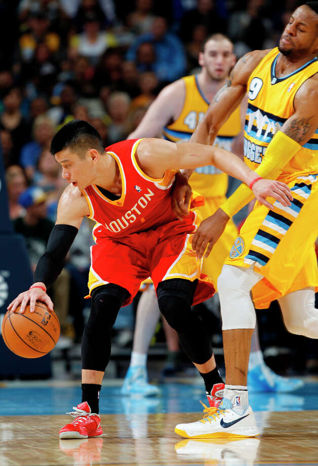 Rockets guard Jeremy Lin picks up a loose ball as Andre Iguoudala of the Nuggets defends. Photo: David Zalubowski, Associated Press