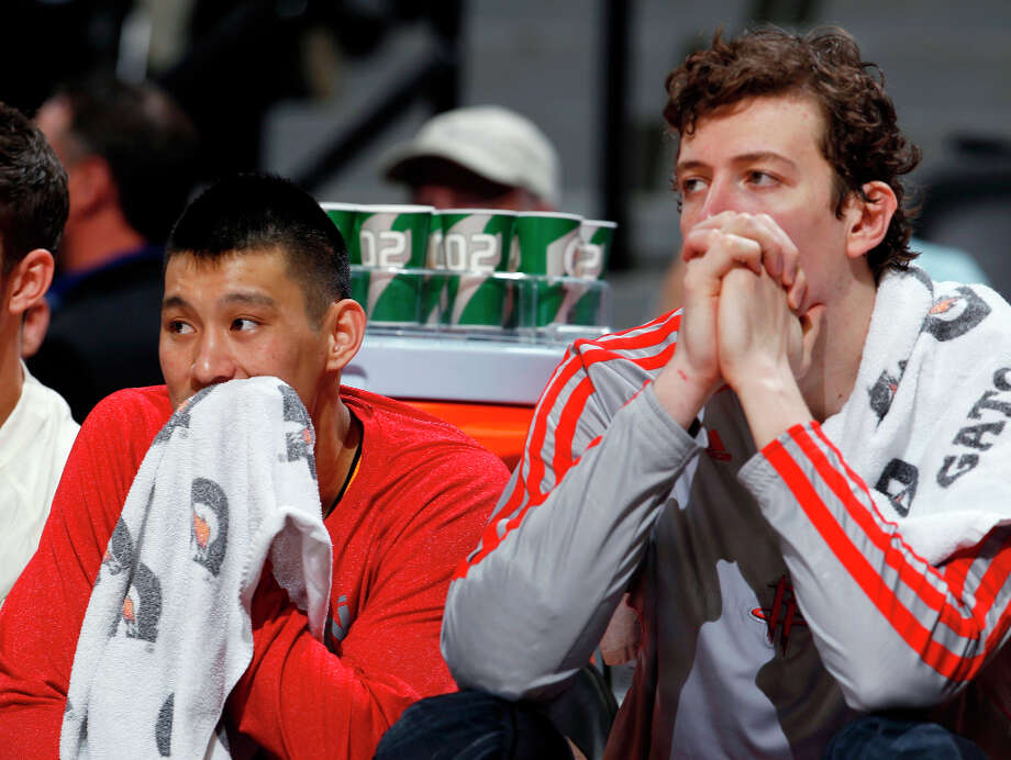 Jeremy Lin and Omer Asik of the Rockets watch from the bench during the fourth quarter. Photo: David Zalubowski